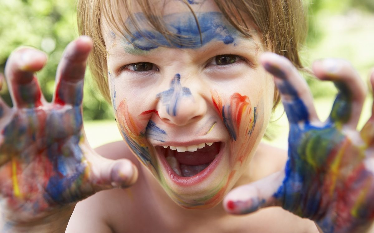 Portrait Of Boy With Painted Face and Hands Smiling To Camera.