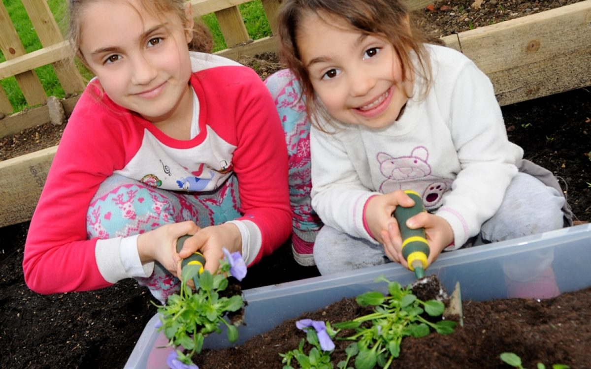 Elif, 8, and Ayse, 3, show off their planting skills